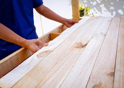 Man assembling wooden slats for making floor of kids playhouse in garden. Woodwork at house. Handmade wooden playhouse.