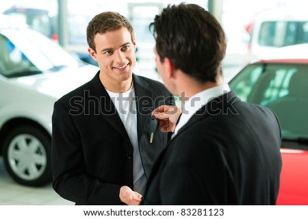 Man at a car dealership buying an auto, the sales rep giving him the key