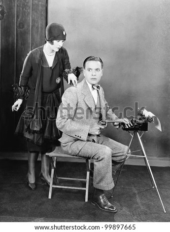 Man at a typewriter holding a gun and a  woman tapping on his shoulder
