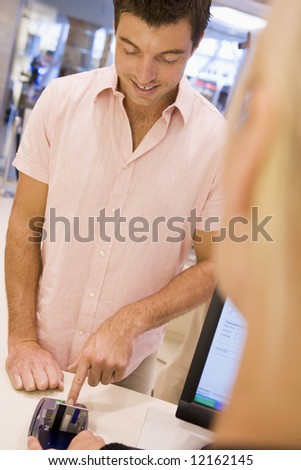 Man at checkout paying with credit card