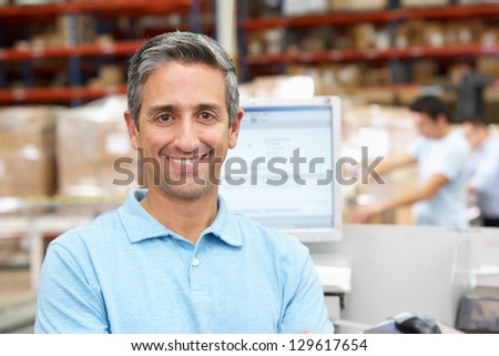 Man At Computer Terminal In Distribution Warehouse