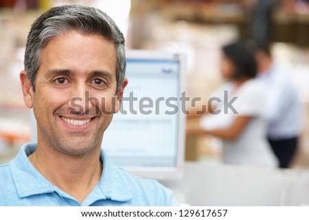 Man At Computer Terminal In Distribution Warehouse