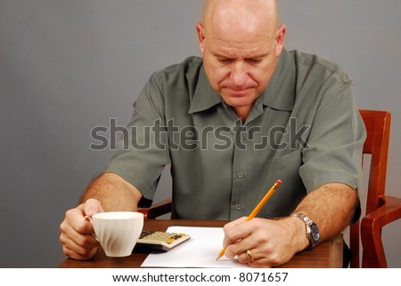 Man at Desk Drinking Coffee Working on Budget with Calculator