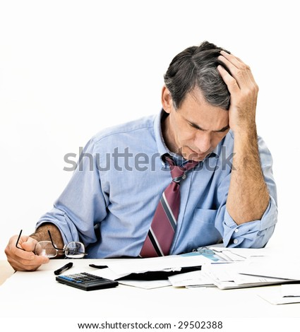 Man at desk in shirt and tie holding his head and worrying about money.