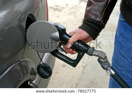 Man at gas pump putting gas into his SUV