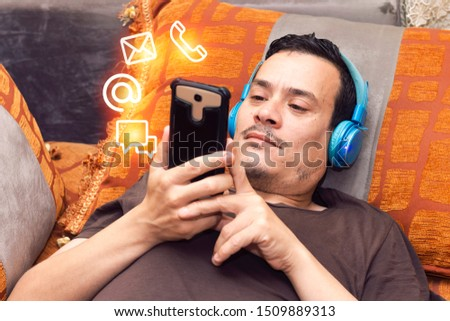 Man at home on moroccan sofa using  a  smartphone with  icon mobile phone, mail, telephone and address. Customer service call center contact us concept