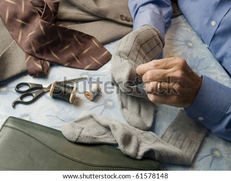 man at home table darning socks