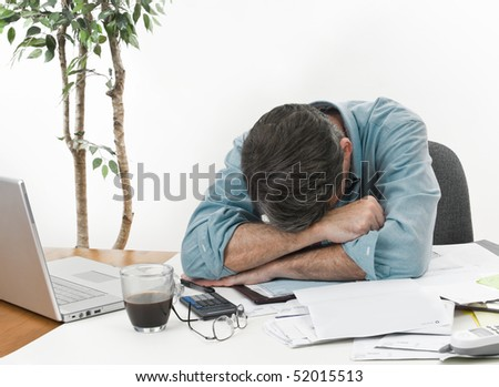 Man at office desk in with his head on his arms, worrying about paying the bills.