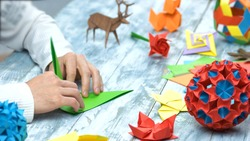Man at origami folding lesson. Collection of beautiful origami figurines on wooden table. Traditional origami paper folding.