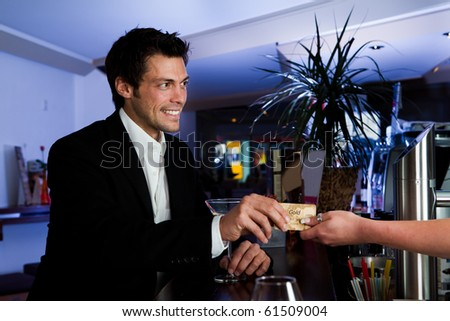 Man at the bar paying with gold credit card