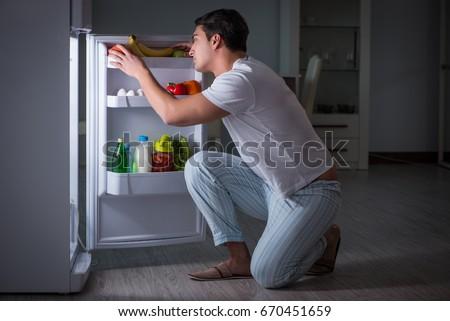 Man at the fridge eating at night Сток-фото ©
