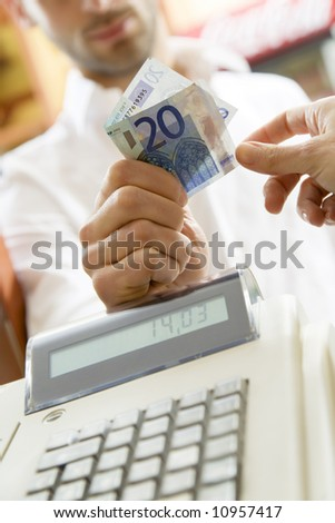 man at the supermarket giving 20 Euro to the cashier