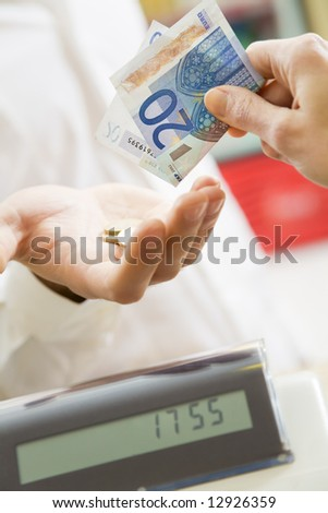 man at the supermarket paying 20 Euro to the cashier