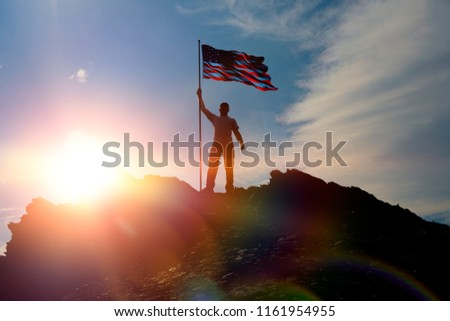 Man at the top of the mountain with the flag of the United States of America, against the sky with sunset. Independence Day, patriot, military. #1161954955