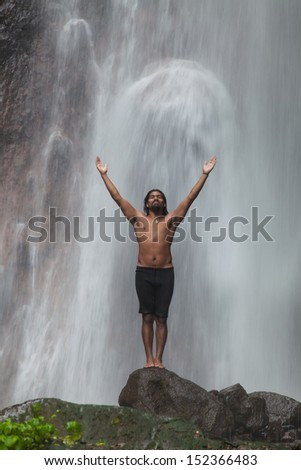 Man at waterfall raising his hands in feeling closer to nature