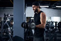 Man athlete keeping twelve and a half kilogram hand weights in each arm and doing heavy lifting