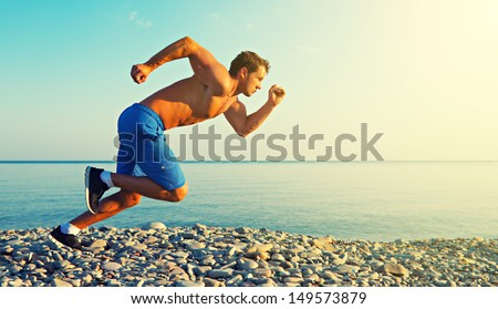 man athlete running by the sea at sunset outdoors