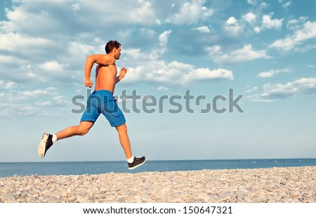 man athlete runs by the sea at sunset outdoors