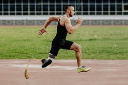 man athlete with prosthetic legs running in track stadium