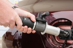 Man attaches nozzle to car while refuelling a hydrogen powered vehicle