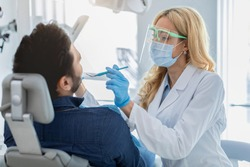 Man attendist dental clinic, sitting in chair, having regular checkup. Female dentist in face mask and protective glasses making treatment for male patient, holding dental tools, copy space