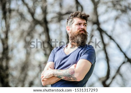 Man attractive bearded hipster posing outdoors. Confident posture of handsome man. Guy masculine appearance with long beard. Barber concept. Beard grooming. Beard care. Masculinity and manliness.