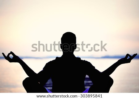 man backlight making yoga in front of the sea