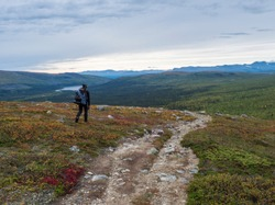 Man backpack hiker at Kungsleden trail admiring nature of Sarek in Sweden Lapland with mountains, river and lake, birch and spruce tree forest. Early autumn colors, blue sky white clouds.