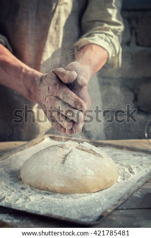 man Baker and his hands over the bread from whole wheat flour (to oven). flour, rustic style