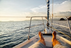 Man bare feet on a luxury deck of a yacht at sea. Relax on your little yacht.