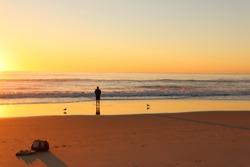 Man beach fishing with golden sunrise background