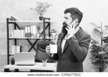 Man bearded businessman hold cup and smartphone. Mobile call. Start day with coffee. Coffee relaxing break. Boss enjoying energy drink. Coffee is pledge of successful negotiations. Caffeine addicted.