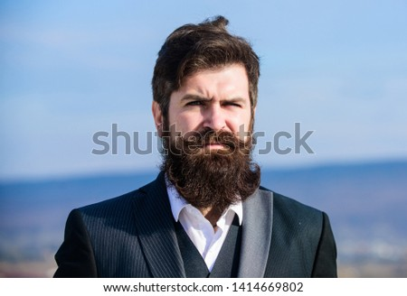 Man bearded hipster wear formal suit blue sky background. Vintage style long beard. Facial hair beard and mustache care. Beard fashion trend. Invest in stylish appearance. Grow thick beard fast.