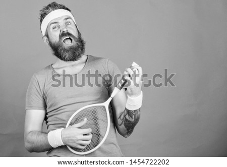 Man bearded hipster wear sport outfit. Having fun. Tennis active leisure. Athlete hipster hold tennis racket in hand red background. Tennis player vintage fashion. Tennis sport and entertainment.