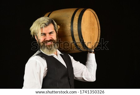 Man bearded hipster wooden barrel for wine black background. Advice on Buying Old and Rare wines. Fermentation product. Natural wine. Winery concept. Homemade wine. Producing wine family tradition.