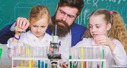 Man bearded teacher work with microscope and test tubes in biology classroom. How to interest children study. Explaining biology to children. Fascinating biology lesson. School teacher of biology.