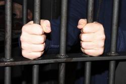 Man behind jail bars reaching out