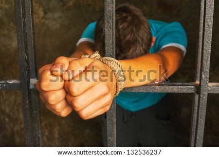 Man behind the bars with hands tied up with rope