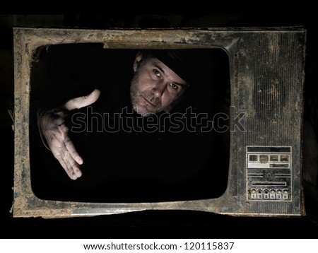 Man behind TV screen. A man behind the TV screen in dark background that wants to handshake the viewers