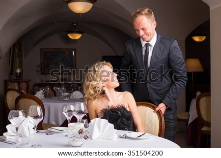 Man being a gentleman and helping woman with her chair
