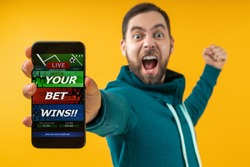 Man being happy winning bet in online sport gambling application on mobile phone, screaming and clencing his his fist. Close up cropped shot. Focus is on hand. Isolated over yellow background.