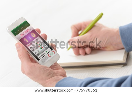 Man betting on sports, over shoulder view on hand with smartphone with scores and other hand taking notes
