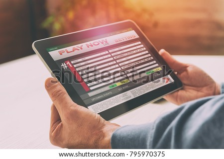Man betting on sports, over shoulder view on tablet with scores