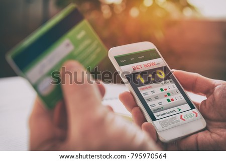 Man betting on sports with credit card, over shoulder view on hand with smartphone