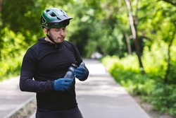 Man biker in helmet drinking water, cycling in public park or down country side, copy space