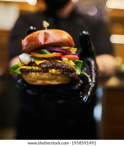 Man Black Gloves Holding Burger Hands Juicy Burger Close Appetizing burger. Stock photo ©
