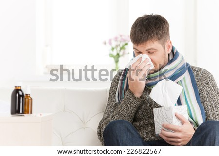 Man blowing his nose in his living room. closeup on guy sitting on sofa and sneezing #226822567