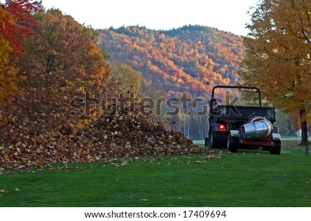 Man blowing leaves off golf course fairway with powerful blower.