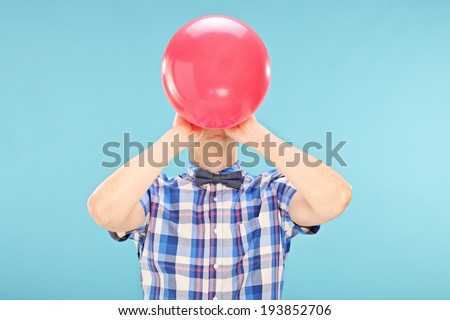 Man blowing up a balloon on blue background Сток-фото ©
