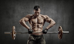 man bodybuilder, execute exercise with weight on grey wall background with empty space.  Gym concept